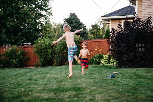 Boys playing in backyard in summer