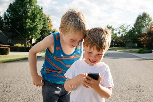 Boy watches younger brother playing game on smartphone