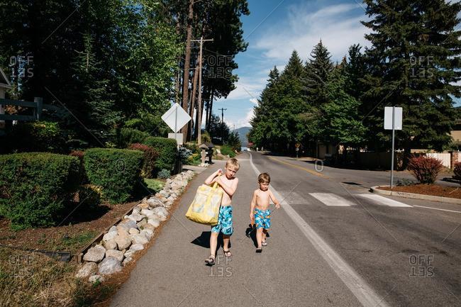 Two young boys in swim trunks walking in street