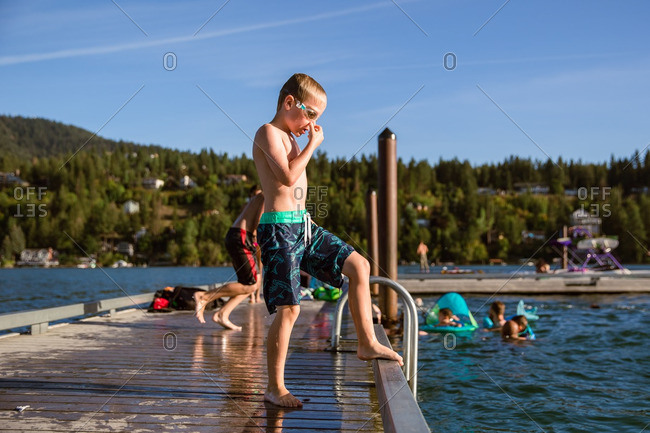 Boy getting ready to jump off lake dock