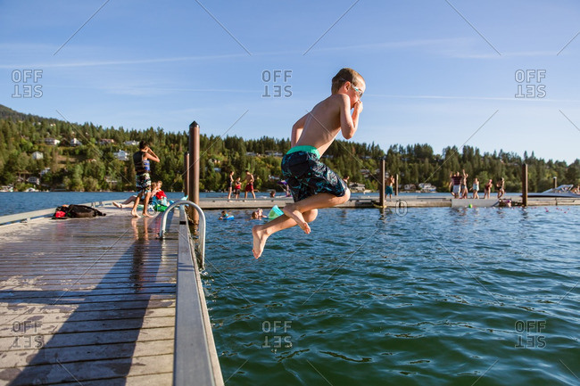 Boy jumping off dog in lake