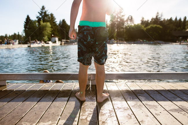 Back view of boy standing on dock at lake