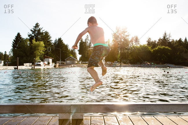 Young boy jumping off dock into lake