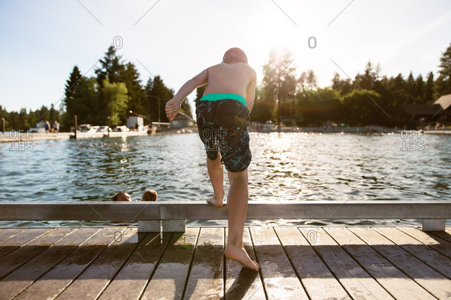Young boy preparing to jump off dock