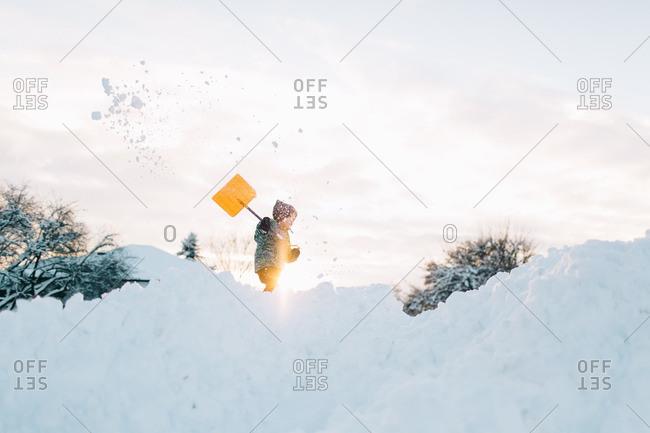 Young boy shoveling snow at dusk