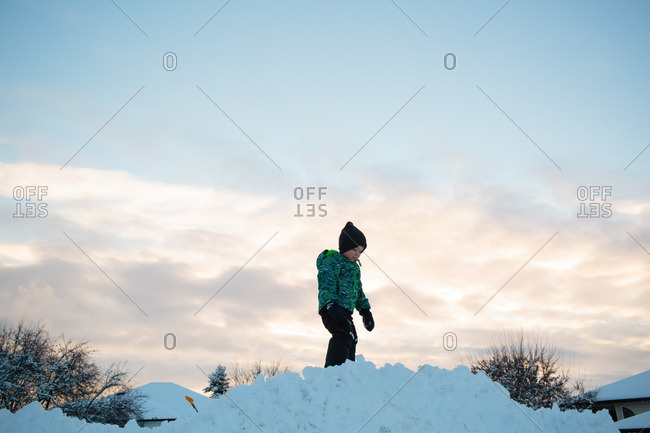Boy standing on pile of snow at dusk