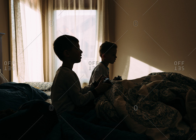 Silhouette of two boys sitting in a bed playing video games