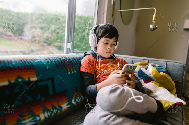 Young boy listening to music on Smartphone with headphones