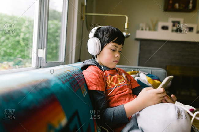 Boy listening to music on his cell phone with headphones