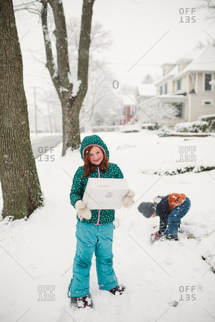 Girl holding package while little brother plays in the snow