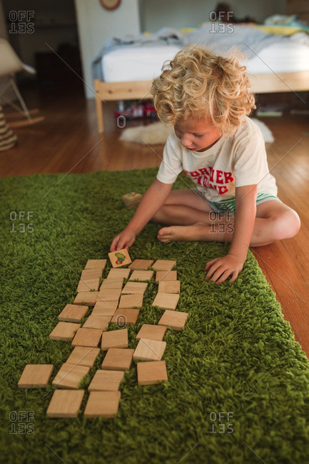 Boy playing wooden memory game on a green rug