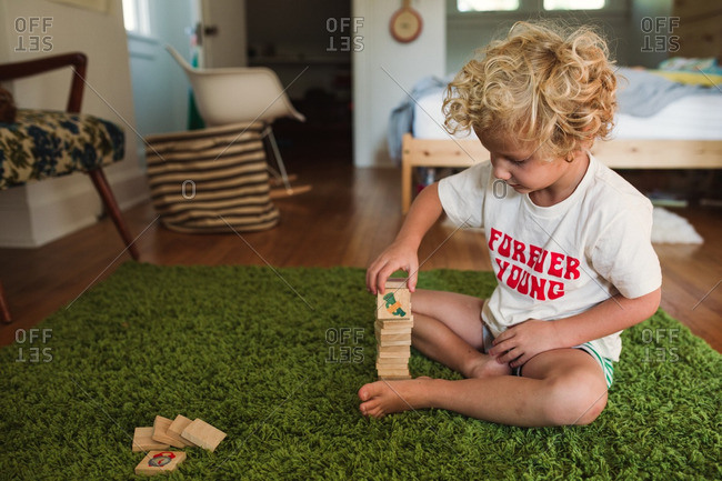 Boy stacking wooden tiles on a green rug