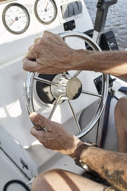 Hands of a captain driving his yacht