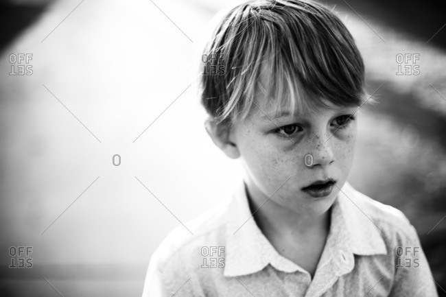 Portrait of a little boy with freckles in black and white
