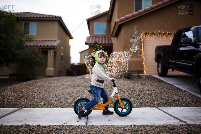 Toddler boy riding bike on a residential sidewalk