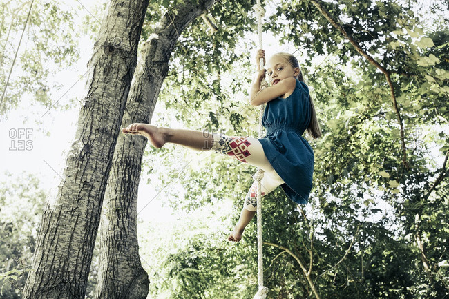 Girl hanging from rope on tree