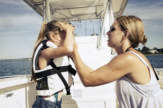 Mother applying sunscreen to face of daughter on boat