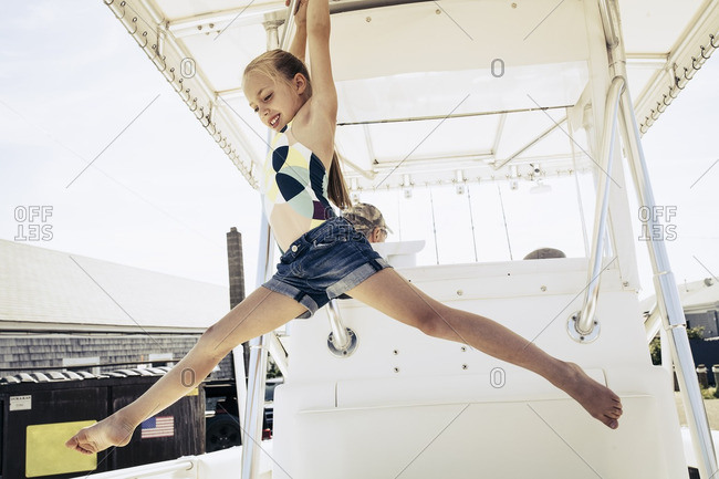 Girl hanging from pole on boat