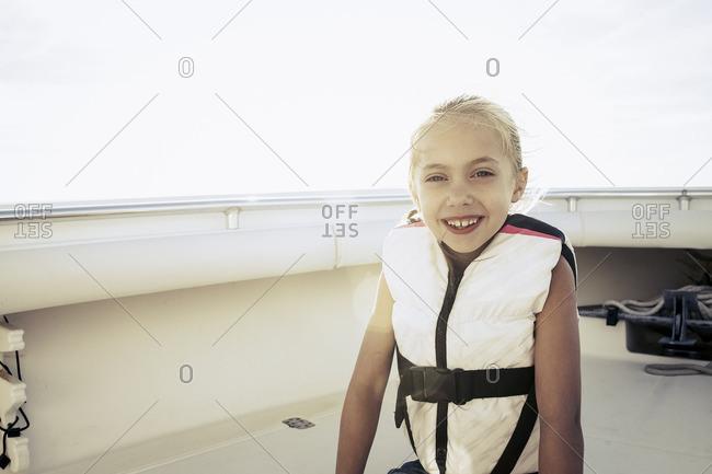 Smiling girl wearing life-jacket on boat