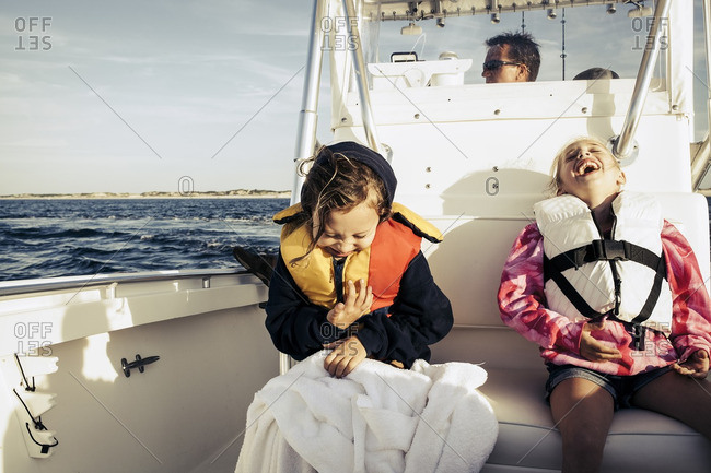 Laughing girls wearing life-jackets on boat