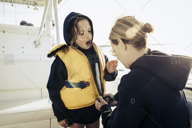 Mother zipping life-jacket for daughter on boat