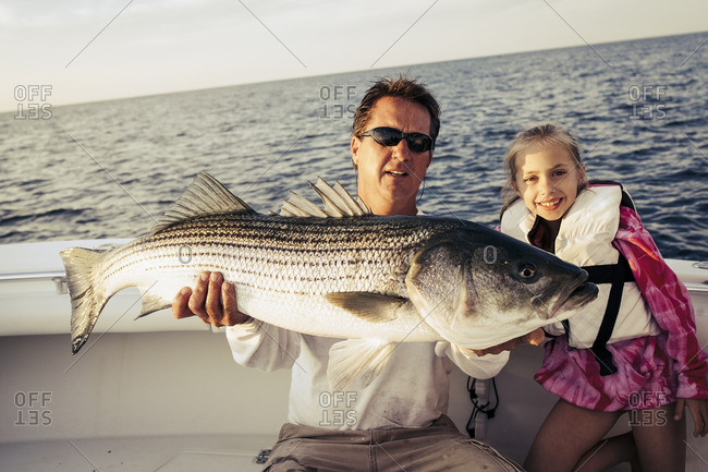 Father and daughter showing fish on boat