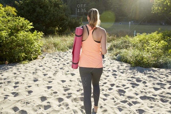 Woman carrying exercise mat on beach