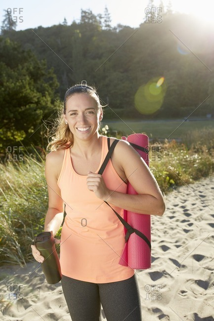 Smiling woman carrying exercise mat on beach