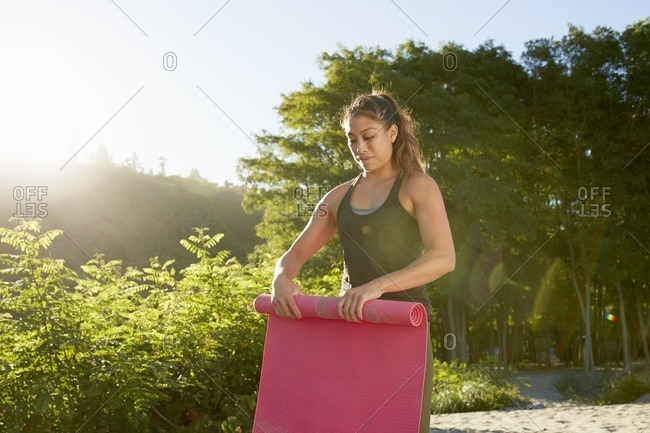 Woman rolling exercise mat on beach