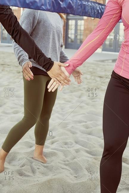 Women clapping hands under beach volleyball net