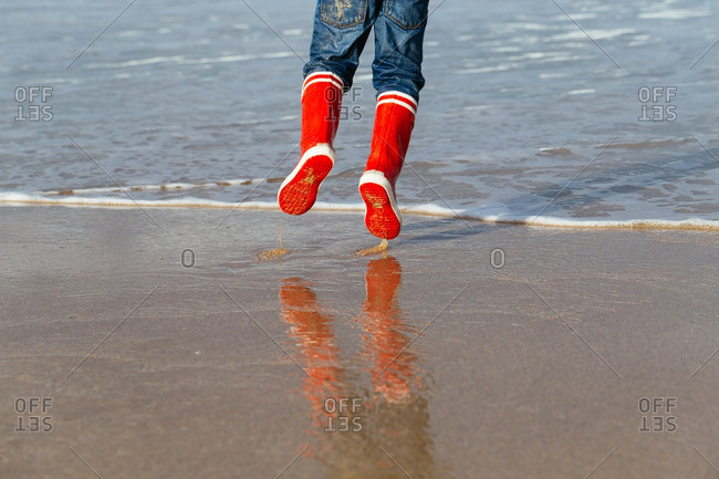 Child wearing red boots hopping on the seashore