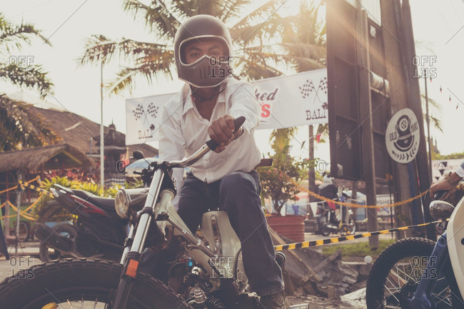 Bali, Indonesia - October 2, 2016: Man sitting on a motorbike