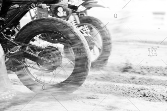 Motorbikes spitting dust behind spinning tires