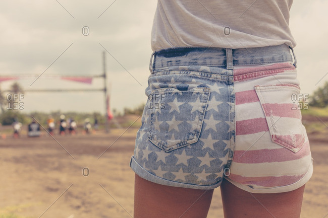 Woman wearing American flag shorts watching a motocross race