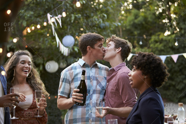 Friends celebrate with gay couple at outdoor backyard party