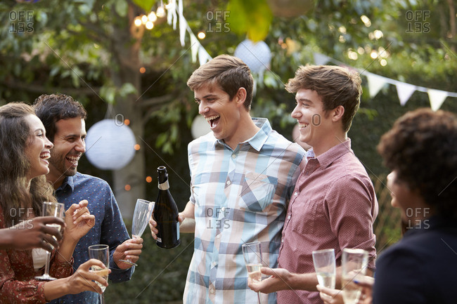 Gay couple celebrate with gay couple at outdoor backyard party