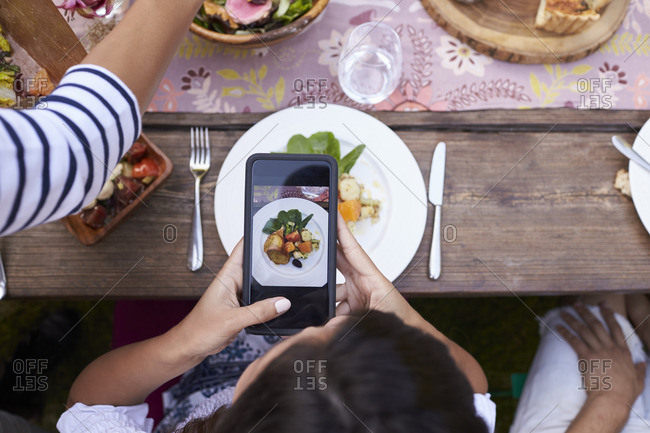 Guest taking picture of food on mobile phone at party