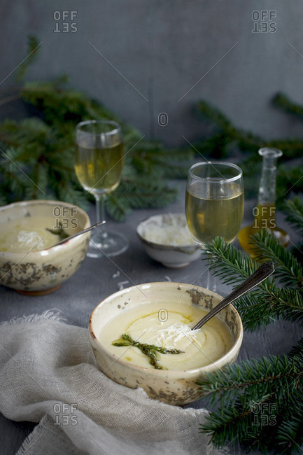 Asiago White Bean Soup with Thyme Oil served in ceramic bowls with white wine.  Photographed from front view on a gray background.