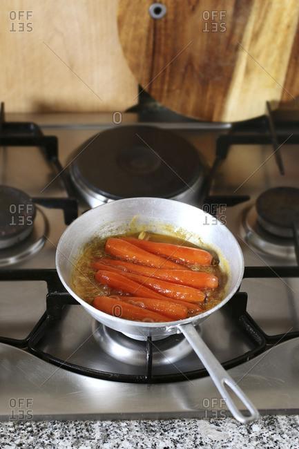 Honey glazed Carrots in pan simmering in freshly squeezed orange juice to glaze