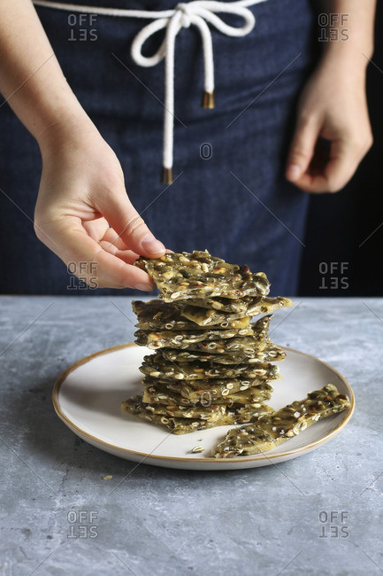 Female hand staking pieces of pumpkin seed brittle on a plate