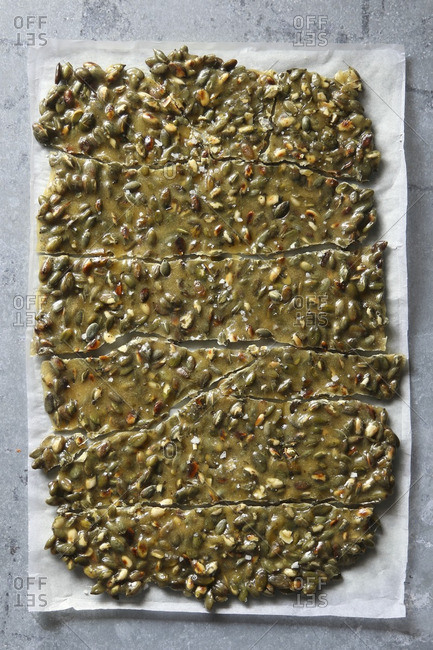 Toasted Pumpkin seed brittle on a parchment paper. Top view