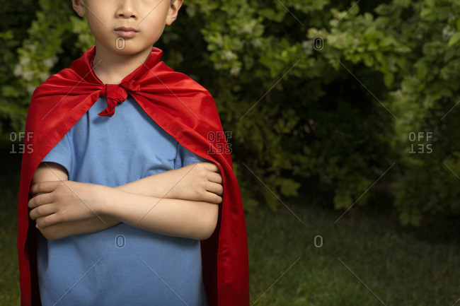 Boy In Red Cape Playing In Garden