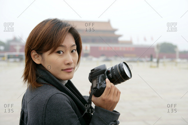 Portrait of a young woman holding camera, Tiananmen , Beijing, China