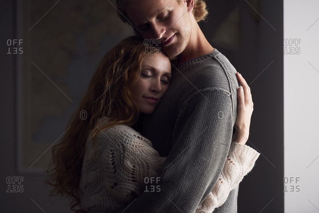 Beautiful couple embrace at home
