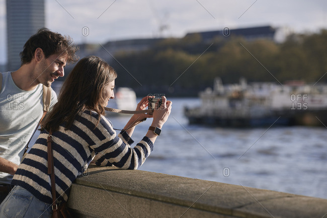 Tourists taking photo of travel destination with smart phone