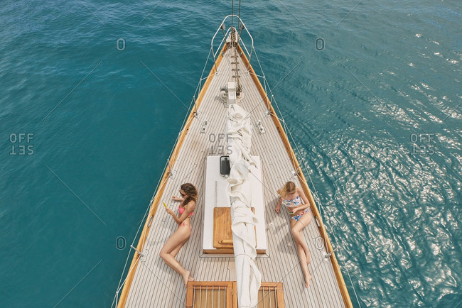 Beautiful girl friends on sailboat using smart phone