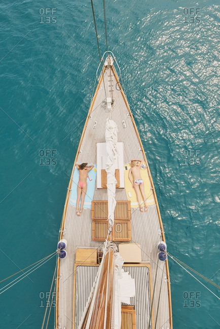 Beautiful girl friends tanning on sailboat in ocean from overhead