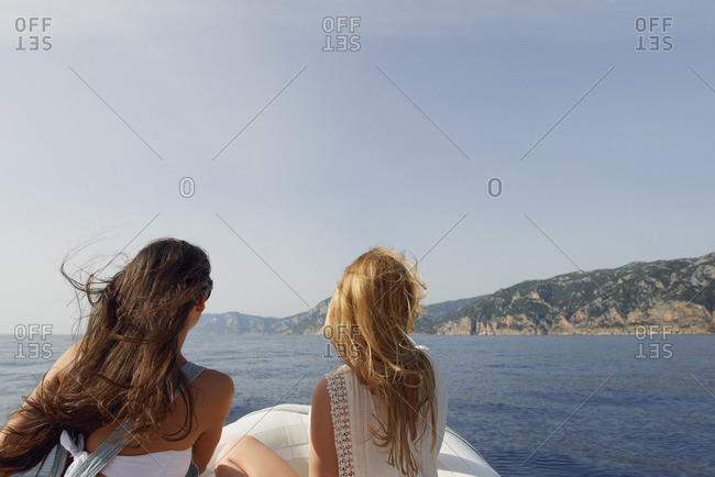 Beautiful girl friends travel on speed boat to paradise island for relaxing nature tourist destination vacation discover explore