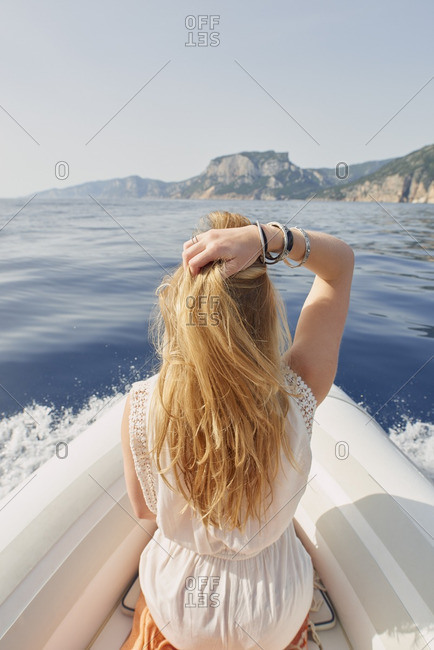 Beautiful woman on speed boat driving to beach