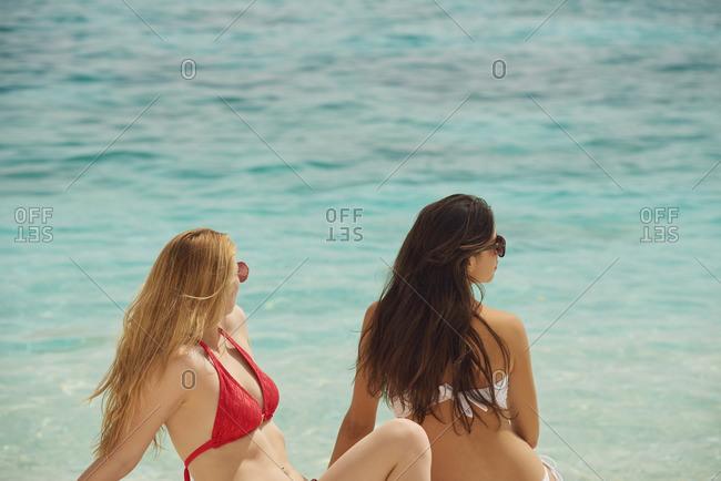 beautiful girl friends relaxing on beach